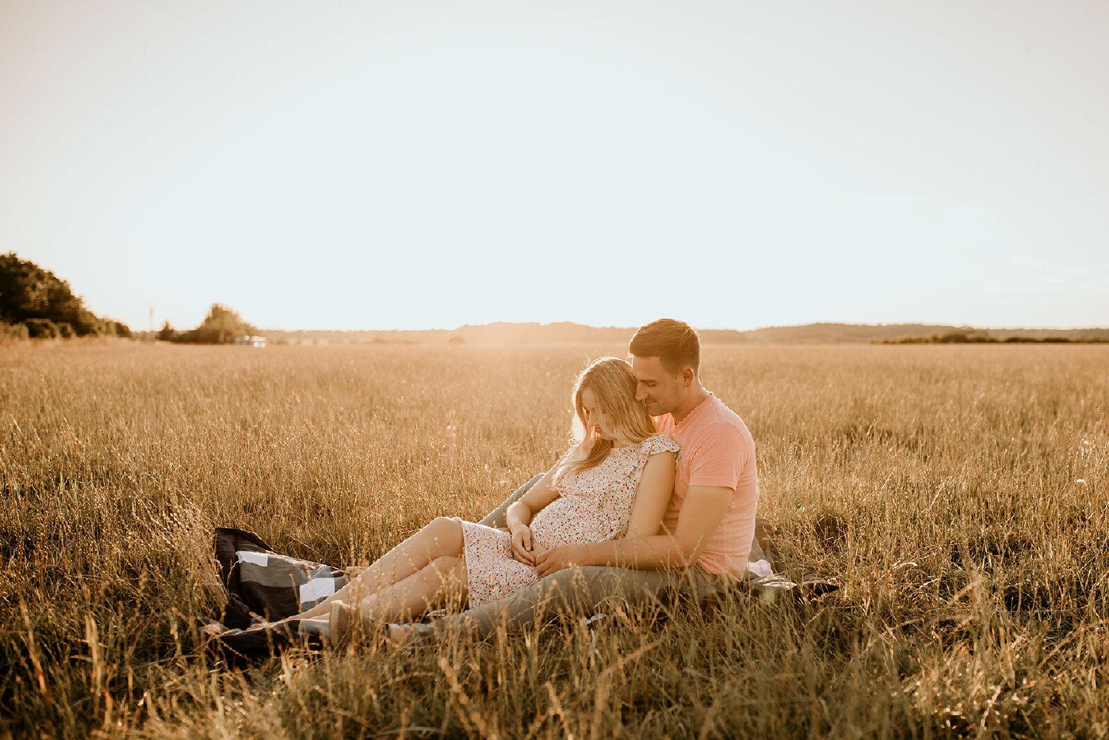 zwangerschapsfotografie buiten met partner in grasveld
