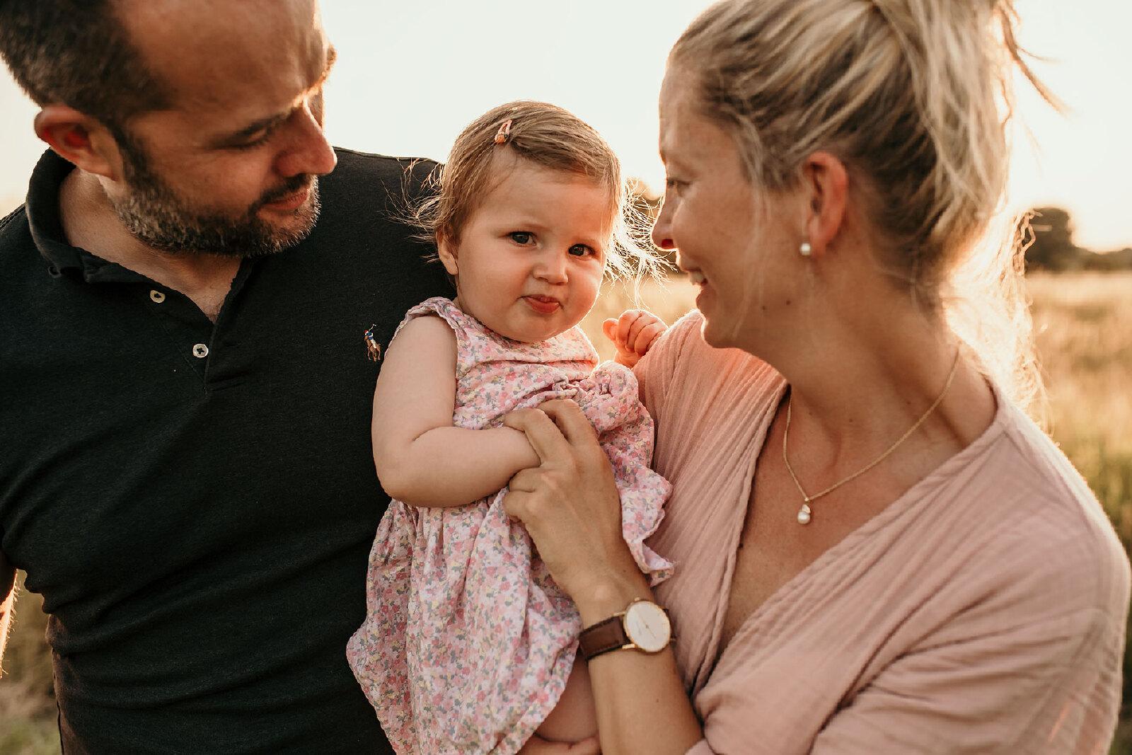 blije baby gezicht fotoshooting met ouders buiten in Haaksbergen