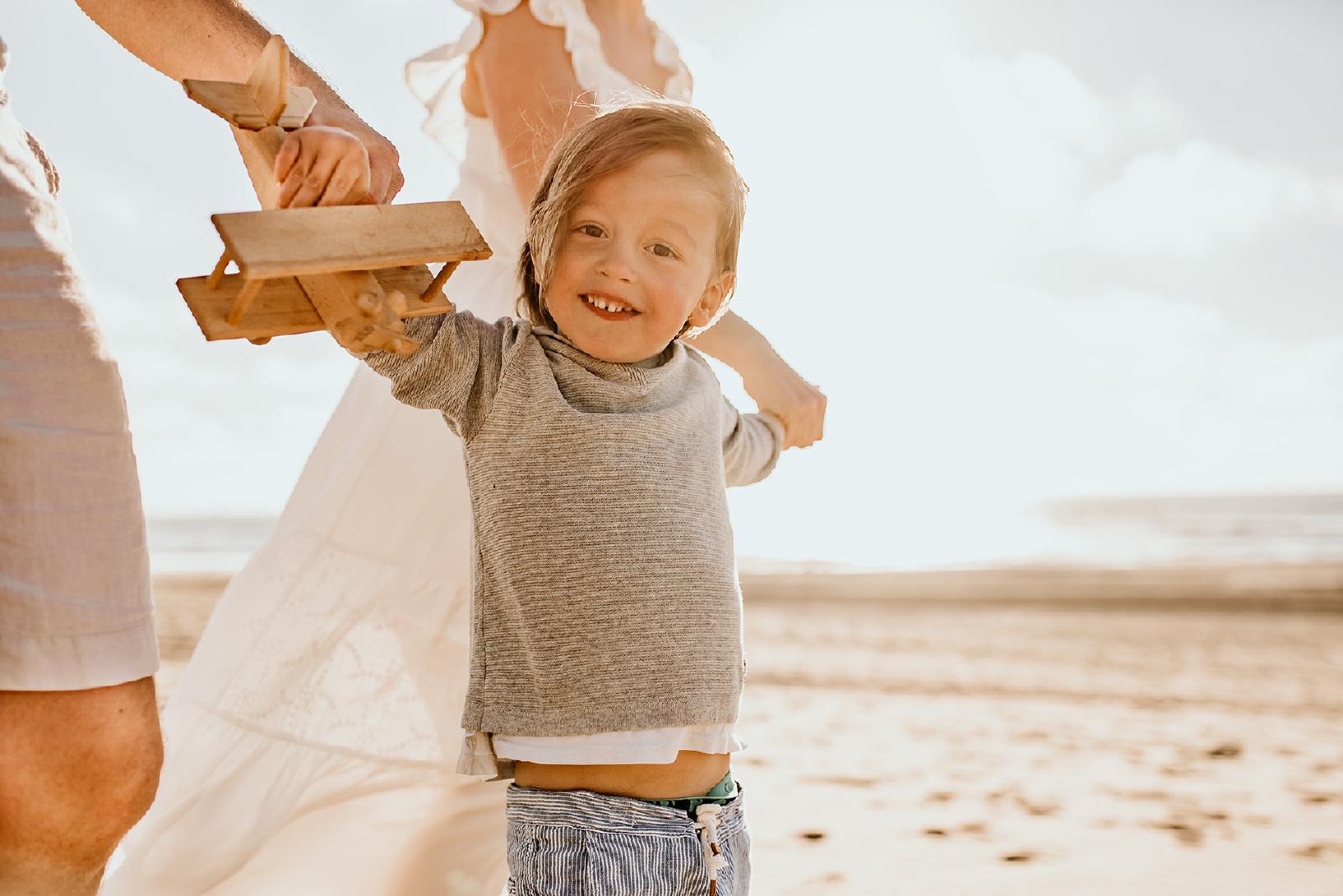jongen aan de hand van ouders op de strand