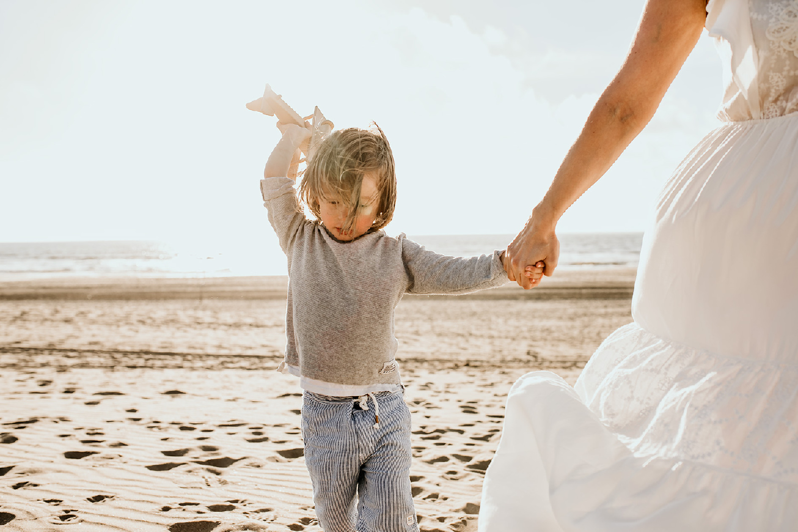 jongen aan de zee mama's hand