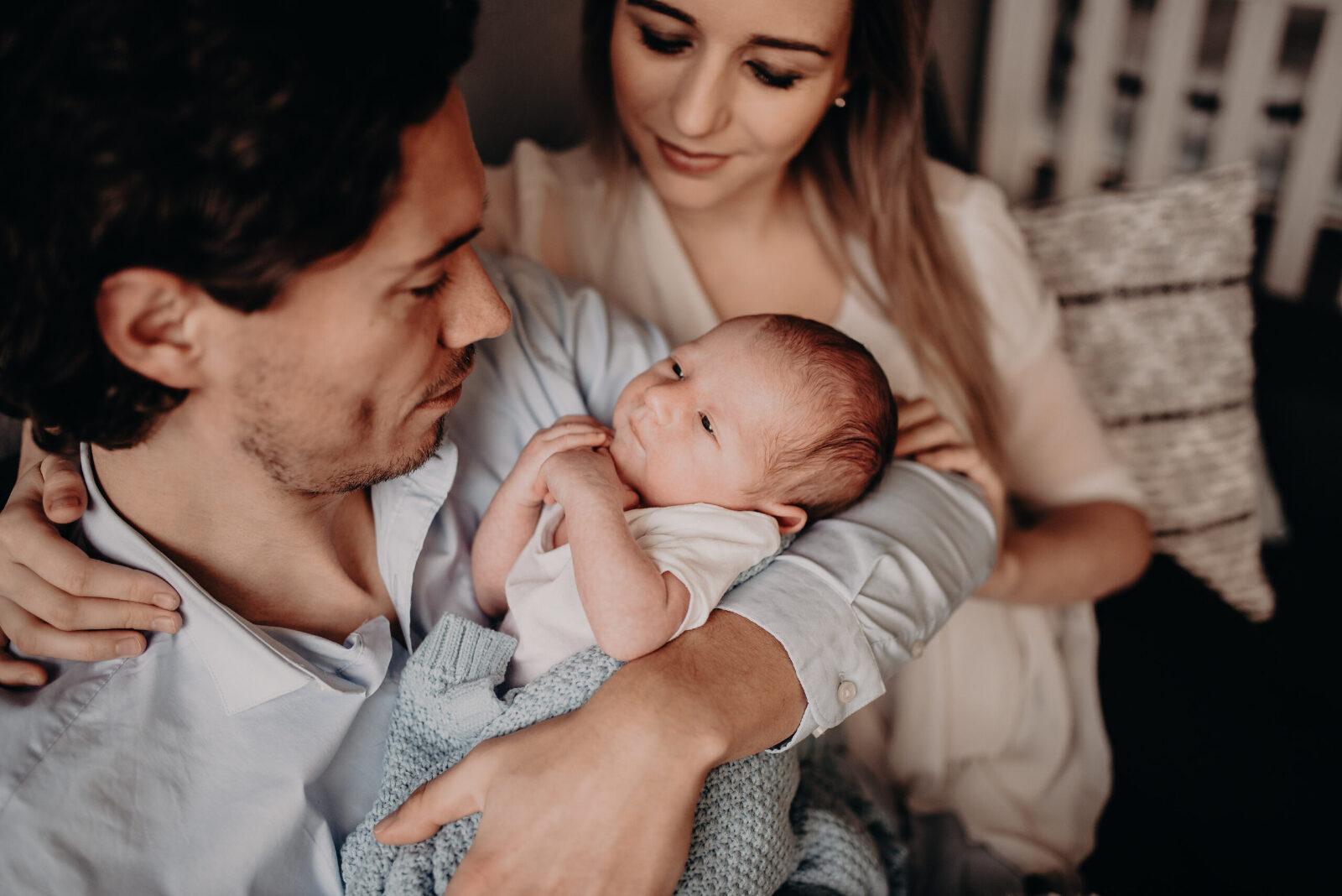 baby op arm bij papa mama op achtergrond